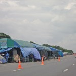 Flood victims setting up temporary shelters by the side of the road.